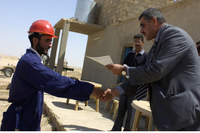A student is presented his certificate of training completion by Mayor Salih Hassan Ali, of Qayyarah, during the graduation ceremony May 24. The students' training started in December 2008 and continued while they were building the Tal Abtha Road.