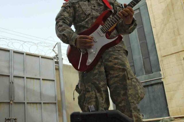 Spc. Victor Lararamirez plays his electric guitar for Sevendust, a hard rock band from Atlanta, who paid a visit to Company D, 1st Battalion, 12th Cavalry Regiment, 3rd Heavy Brigade Combat Team, 1st Cavalry Division. The Soldiers couldn't travel to Forward Operating Base Marez to see the band play a concert May 26, so instead the band brought their charisma to the troops at Combat Outpost Scorpion.