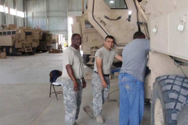 Company F, 949th Brigade Support Battalion's Sgt. Anthony Fowlkes, a native of Baltimore, Md., and Spc. David Arias, a Red Oak, Texas native, learns how the Caiman Mine-Resistant Ambush-Protected vehicle operates during a vehicle equipment course at Camp Taji, Iraq.
