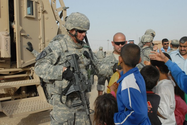 Sgt. Jeremy Brister, a Pleasanton, Texas, native and an infantryman with Company C, 1st Battalion, 8th Cavalry Regiment, 2nd Brigade Combat Team, 1st Cavalry Division, distributes food to children in the village of Qushquaya, Iraq, May 29.