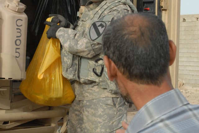 Pfc Anthony Mariscal, a Houston native and a tanker mechanic with Company C, Battalion, 8th Cavalry Regiment, 2nd Brigade Combat Team, 1st Cavalry Division, distributes food from the back of his vehicle in the village of Qushquaya, Iraq, May 29. Mariscal, along with other Soldiers from his platoon, distributed more than 100 bags of food to residents of the village.