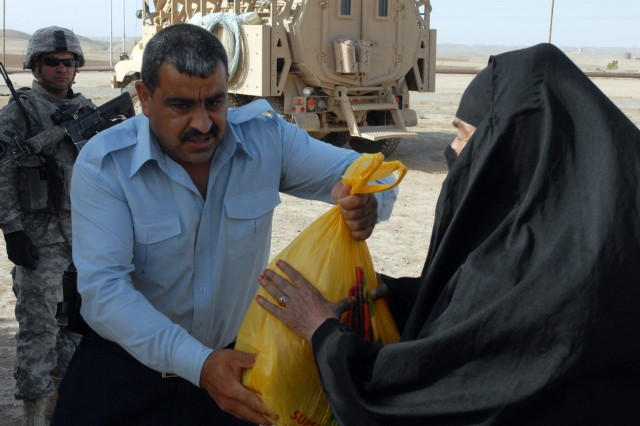 An Iraqi policeman assisted by Soldiers from Company C, Battalion, 8th Cavalry Regiment, 2nd Brigade Combat Team, 1st Cavalry Division, distributes food to an Iraqi woman in the village of Qushquaya, Iraq, May 29.