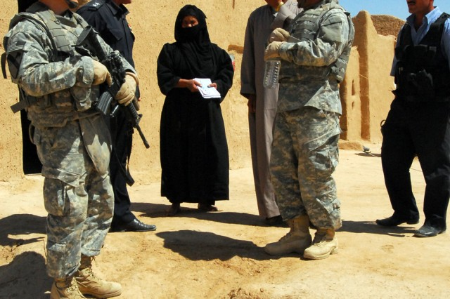 Lt. Abbas (upper left) of the Daquq, Iraq Police and 1st Lt. Christopher Minter (left), from New Kent, Va., and a platoon leader in C Troop, 4th Squadron, 9th Cavalry Regiment, 2nd Brigade Combat Team, 1st Cavalry Division, speak with residents near the village of Zalla Al Sabaee in Kirkuk province during a combined visit to the village to conduct an assessment of essential services, May 31.