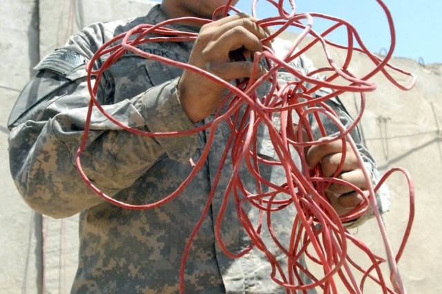 BAGHDAD - Dallas, Texas native, Pfc. Blaine Hancock, a communication specialist with Company E, 1st Battalion, 5th Cavalry Regiment, attached to the 1st Brigade Combat Team, 1st Cavalry Division, rolls up the computer wire from the old containerized housing units, June 2.  Company E Soldiers are currently moving out of Joint Security Station Basateen in accordance with the Security Agreement that states U.S. combat troops will be out of all Iraqi cities by June 30.