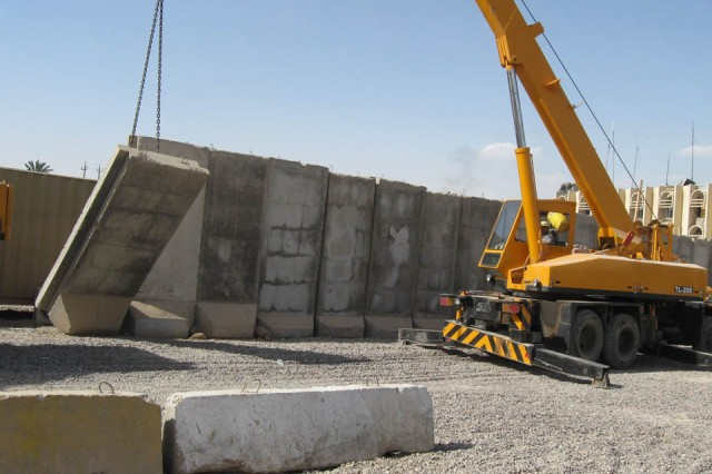 BAGHDAD- An Iraqi contractor pulls down a concrete T-wall during the process of moving U.S. troops out of Joint Security Station Basateen, June 2. In order to comply with the Security Agreement, which states all U.S. combat troops will move out of the cities by June 30, Soldiers of Company E, 1st Battalion, 5th Cavalry Regiment, attached to the 1st Brigade Combat Team, 1st Cavalry Division,  are moving on to JSS War Eagle.