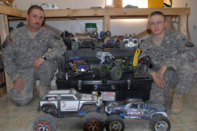 "BAGHDAD - Pineville, La. Native, Spc. Krider McCan (left) and Spc. Michael Hanks, from Lecompte, La., both members of the 225th Engineer Brigade, show off their collection of remote control cars.  Their cars, which come in various shapes and styles, can reach top speeds up to 70mph when properly tuned up. McCan and Hanks are just two members of the brigade's ""Team Tango"", who compete every Sunday in a friendly racing competition between other deployed service members at their local dirt race track on Camp Liberty, Iraq."