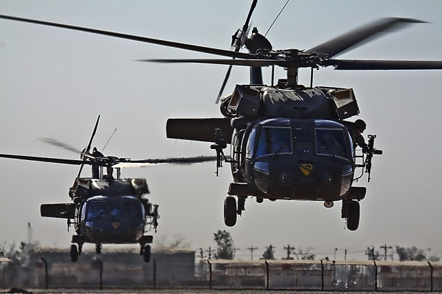 CAMP TAJI, Iraq-Two UH-60 Black Hawk helicopters from 3rd Battalion, 1st Air Cavarly Brigade, 1st Cavalry Division, Multi-National Division-Baghdad, depart for an air assault mission packed with Soldiers from 1st Battalion, 112th Infantry Regiment, 56th Stryker Brigade Combat Team, from Camp Taji, Iraq, June 3. 1st ACB aviators provide arieal coverage for the Soldiers of the 56th BCT while they conduct ground operations.