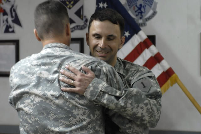 BAGHDAD - Col. Joseph Martin (left), a native of Dearborn, Mich., commander, 2nd Heavy Brigade Combat Team, 1st Infantry Division, Multi-National Division - Baghdad, hugs Lt. Col. Frank Tank, a native of Minot, N.D., intelligence officer-in-charge, 2nd HBCT, at Camp Liberty,Iraq, June 1. Tank was promoted to the rank of Lt. Col., which indicates his position as a senior field-grade officer.