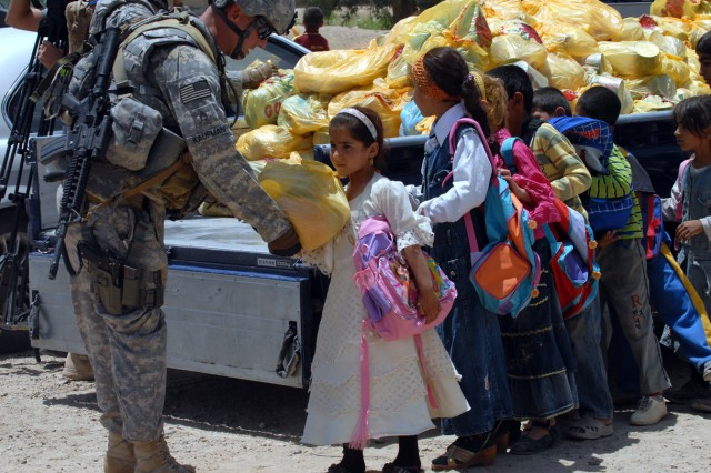 """BAGHDAD - Staff Sgt. Brian Kaufman, a native of Marcelous, N.Y. and civil affairs team sergeant assigned to A Company, 403rd Civil Affairs Battalion gives a little girl a bag of food after the ground breaking ceremony at the Zoba Village High School, June 4.  """"The people here haven't really seen Coalition forces in over two years,"""" said Kaufman."""