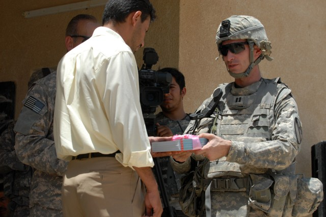 BAGHDAD - Capt. Jeremy Roy (right), a native of Indianapolis and commander of A Company, 2nd Battalion, 8th Cavalry Regiment, 1st Cavalry Division, gives a gift to the headmaster of the Zoba Village High School, June 4.  The school will also receive many improvements from the investments the Coalition forces have made.