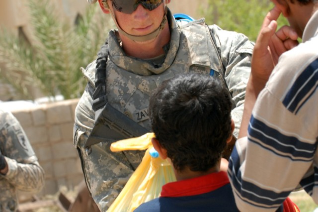 """BAGHDAD - Pfc. Ross Zavoyna, an infantryman assigned to Headquarters and Headquarters Company, 2nd Battalion, 8th Cavalry Regiment, 1st Cavalry Division, gives a child a bag of food for his family after the ground breaking ceremony at the Zoba Village High School June 4.  """"It is nice to see smiles on the kids faces,"""" said Zavoyna."""
