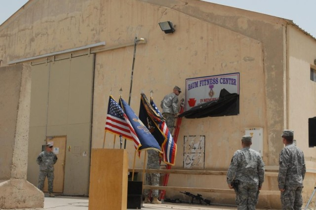 CAMP TAJI, Iraq -Soldiers from 1st Battalion, 111th Infantry Regiment, 56th Stryker Brigade Combat Team, Multi-National Division-Baghdad, unveil the plaque dedicating the Baum Fitness Center.  The gym was named after Staff Sgt. Mark C. Baum, who was killed in action Feb. 21, 2009, north of Camp Taji.