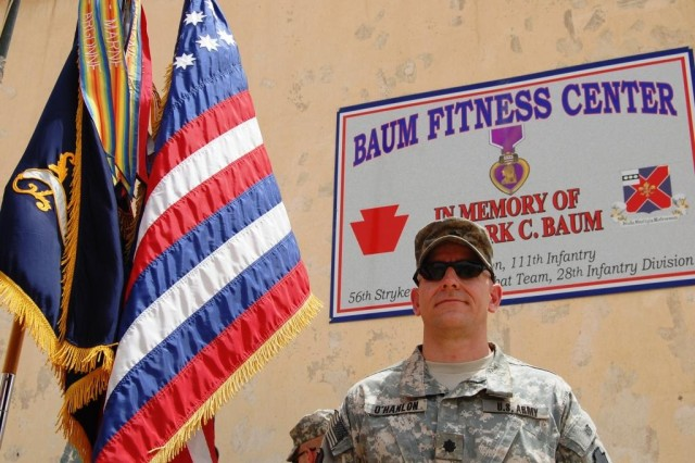 CAMP TAJI, Iraq - Lt. Col Mark O'Hanlon, of Wallingford Pa., stands in front of the plaque at the Baum Fitness Center shortly after it was unveiled.  O'Hanlon is the battalion commander for 1st Battalion, 111th Infantry Regiment, 56th Stryker Brigade Combat Team. The gym was named after Staff Sgt. Mark C. Baum who was killed in action on Feb. 21, 2009, north of Camp Taji.