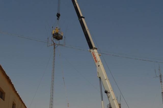 CAMP TAJI, Iraq - A crane lifts a work platform and two 56th Stryker Brigade Combat Team Soldiers to the top of an FM radio antenna, June 4. The Soldiers used the lift to perform maintenance to the antenna.