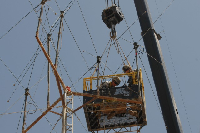 CAMP TAJI, Iraq - Spc. Shawna Teer, (left) of Dallas, Pa., and Spc. Kyle Adamski, of Duryea, Pa., both with Headquarters and Headquarters Company, 56th Stryker Brigade Combat Team, perform maintenance to a radio antenna, June 4. The routine maintenance required the Soldiers to work from a basket suspended next to the top of the 50-feet high antenna.