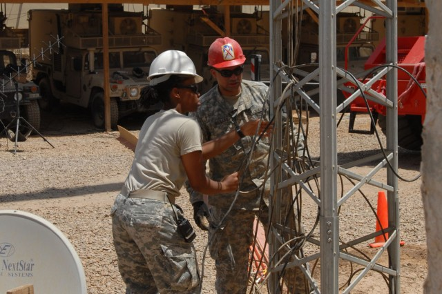 CAMP TAJI, Iraq - Sgt. Shauna Banks (left) and Sgt. Moises Delgado, both of Philadelphia, with Headquarters and Headquarters Company, 56th Stryker Brigade Combat Team, replace wires at the base of an FM radio antenna, June 4.