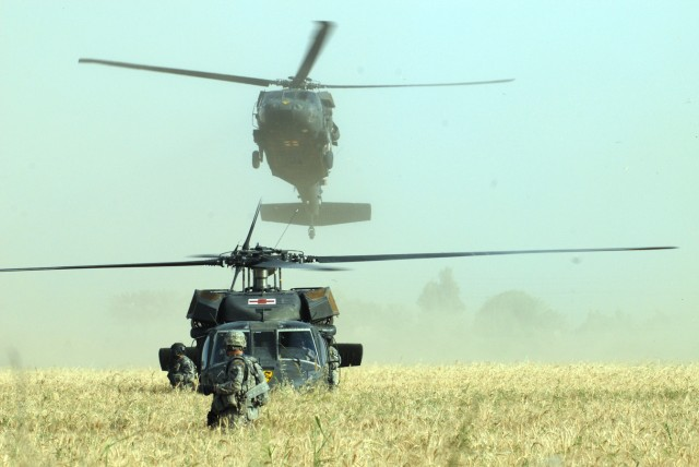 BAGHDAD - A Soldier of B Troop, 2nd Battalion, 8th Cavalry Regiment, 2nd Brigade Combat Team, 1st Infantry Division, communicates with the air cavalry crewmembers in a wheat field to find out a safe time to take the casualties to the UH-60 Blackhawk,...