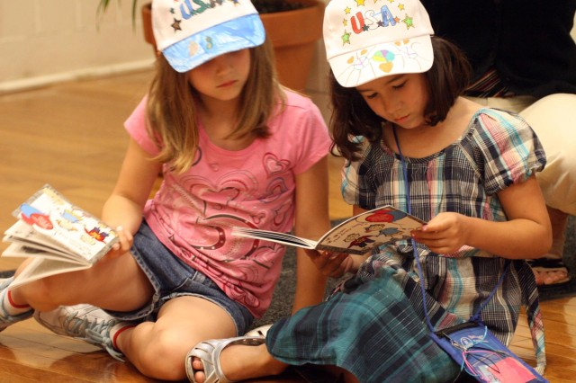 "Kaitlyn Spencer, left, looks on while Reyna Mejia reads ""Sam the Army Dog,"" a special book all West Point children at the Child Development Center and School Age Services received in honor of the Army birthday, June 17 at SAS. The girls just finished up first grade and read the book aloud with classmates during a celebration of the Army's 234th birthday. (Photo by Emily Tower/Pointer View)"