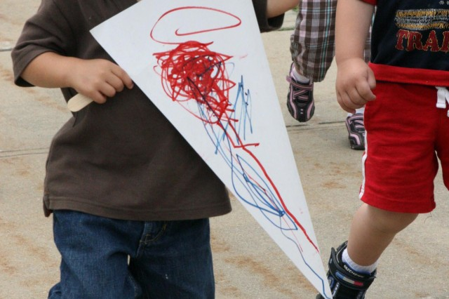 Jase Giglio, 3, shows off his artwork on a banner while making sure a hat he decorated doesn't blow away while marching in a parade to celebrate the Army's birthday June 17 at the West Point Child Development Center.  (Photo by Emily