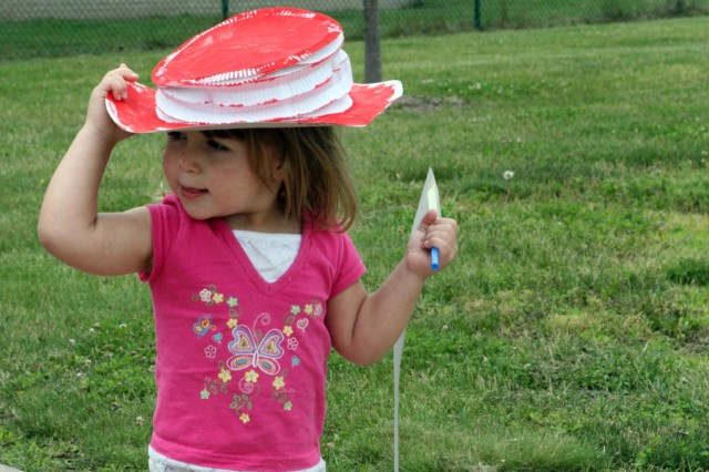 Samantha Curran, 2, makes sure a hat she designed doesn't blow away during a parade to celebrate the Army's birthday June 17 at the West Point Child Development Center. Samantha and her classmates decorated different styles of hats and banners to display during the parade. (Photo by Emily Tower/Pointer View)