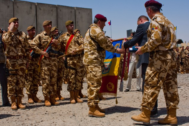 Traian Basescu, the Romanian president, places a streamer on the Red Scorpion Battalion's guidon during the country's end of mission ceremony at Contingency Operating Base Adder and Camp Dracula June 4
