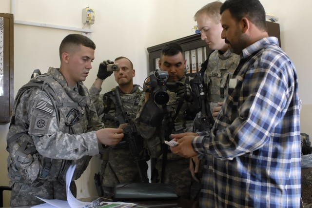 BAGHDAD - Staff Sgt. Samuel Lorenz (left), a native of Mercer, Pa., 2nd Battalion, 8th Cavalry Regiment, attached to the 2nd Heavy Brigade Combat Team, 1st Infantry Division, Multi-National Division-Baghdad, pays an Iraqi businessman money from a small business grant at the Zoba Village Reconciliation Day in Abu Ghraib, June 4. The purpose of the grants is to stimulate the local economy in the village.