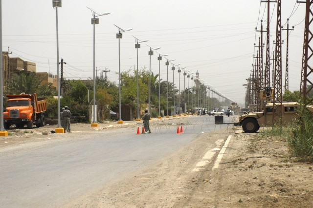 BAGHDAD - Soldiers serving with the 5th Squadron, 4th Cavalry Division, 2nd Heavy Brigade Combat Team, 1st Infantry Division, Multi-National Division-Baghdad, oversee solar lights being installed on a street in the Ghazaliyah neighborhood of northwest Baghdad, May 21. The solar-powered lights alleviate Iraqi's national power grid and keep market streets open later in the evening.