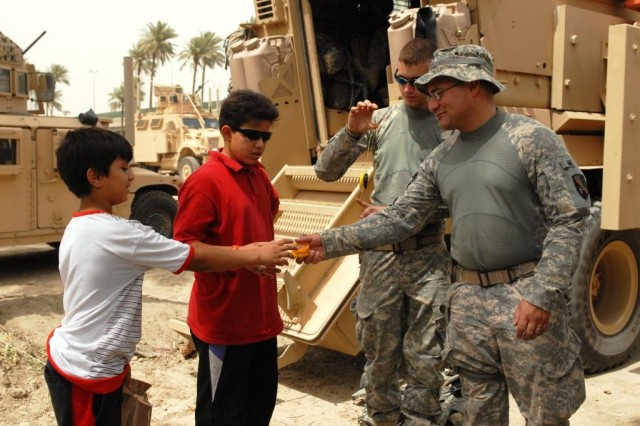 BAGHDAD - Staff Sgt. Adam Sanchez (right), of Alexandria, La., gives his yo-yo to Ali and his brother, Hamza, June 6, outside of Salam Palace in Baghdad. The 225th Engineer Brigade personnel security detachment members use yo-yo's to pass time. When the Iraqi children saw them playing with the yo-yo's, they came to join in the fun.