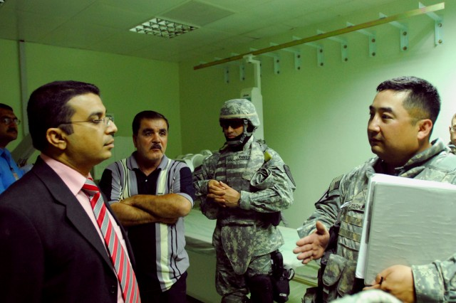 Staff Sgt. Han Parker (right), a San Antonio native and medical sergeant with 2nd Brigade Combat Team, 1st Cavalry Division speaks with hospital director, Dr. Niaz Ameen (left) of the Azadi Hospital in Kirkuk city, Iraq, during a medical assessment of the hospital's X-ray and laboratory departments June 3.