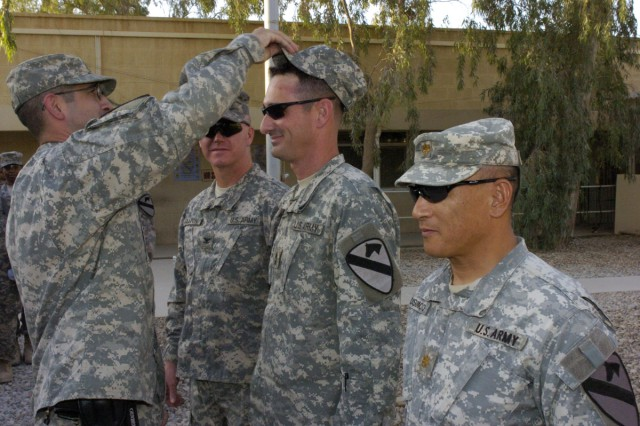 First Sgt. John Palido presents Master Sgt. Kenneth Stone with his new patrol cap with his newly acquired Master Sgt. rank on it during his promotion ceremony on Forward Operating Base Marez.