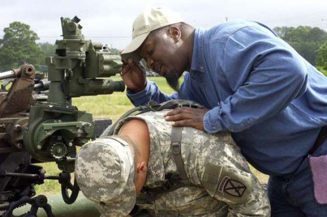 Marvin Johnson, a Fort Sill, Okla. Collective Training and Evaluation Team artillery expert, leans over Spc. Marcus Sims, a cannon crewmember assigned to Battery A, 5th Battalion, 25th Field Artillery, to verify Sims has a good sight picture on his target during training on Red Leg Field here June 4.