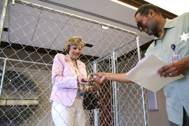 Mary (Cathy) Dickens, Principal Assistant Responsible for Contracting, buys her freedom from Thaddeus Brown, Future Warfare Center, for a $20 immunity bond June 10 during U.S. Army Space and Missile Defense Command/Army Forces Strategic Command's Jail Day Fundraiser. Dickens began working here June 7. Her senior executive service promotion ceremony is planned for 2 p.m., July 10.