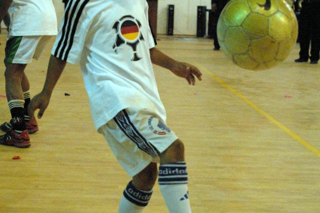 BAGHDAD, Iraq - A young boy from the soccer team kicks a soccer ball as his team shows off their skills. The al-Jazeera gymnasium opening, June 6, will not only help keep children off the streets, but will keep them indoors, supervised and safe, said Dallas, Texas native, U.S. Navy Lt. Erwin Rico, officer in charge of United States Army Corps of Engineers office responsible for the Rusafa area.