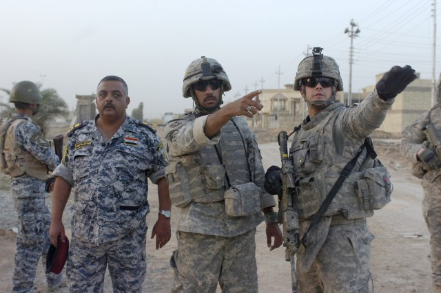 BAGHDAD - 1st Lt. Eric Donahue (right), of Fayetteville, N.C., with the use of an interpreter, tells a National Police officer assigned to the 8th NP Brigade, 2nd NP Division where his men need to be positioned during a time sensitive target training mission, June 10, in the Beladiyat neighborhood, located in the 9 Nissan district of eastern Baghdad. The training event was the first time the combined forces have trained in the region where they operate on a daily basis. Donahue serves as a platoon leader for the scout platoon, 2nd Battalion, 505th Parachute Infantry Regiment, 3rd Brigade Combat Team, 82nd Airborne Division, Multi-National Division-Baghdad.