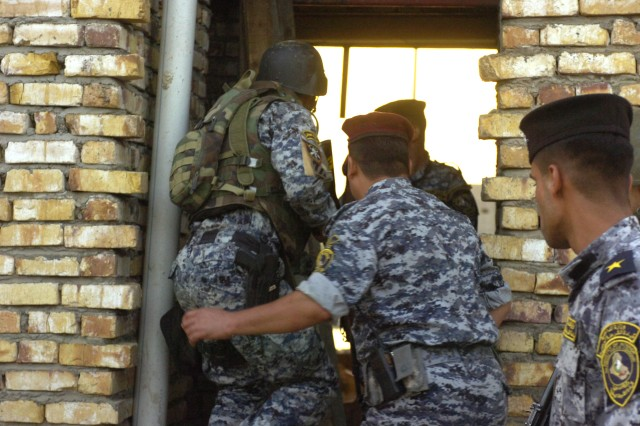 BAGHDAD - National Police officers assigned to the 8th NP Brigade, 2nd NP Division enter a house during a time sensitive target training mission, June 10, in the neighborhood of Beladiyat, located in the 9 Nissan district of eastern Baghdad. Paratroopers assigned to the scout platoon, 2nd Battalion, 505th Parachute Infantry Regiment, 3rd Brigade Combat Team, 82nd Airborne Division, Multi-National Division-Baghdad, trained their Iraqi counterparts on the proper procedures of entering and clearing a house. The training event was the first time the combined forces have trained in the region where they operate in on a daily basis.