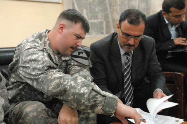 Newport News, Va., native, Capt. Jason Dudley (left), commander for Headquarters Company, 1st Battalion, 5th Cavalry Regiment, attached to the 1st Brigade Combat Team, 1st Cavalry Division, signs the Record of Return of Joint Security Station Suleikh with Sameer al Haddad, the receivership secretariat for the Government of Iraq, June 8.