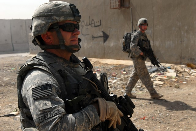 BAGHDAD - Sgt. Jason Traywick (left), a forward observer from Marshville, N.C., and Spc. Justin Davis (right), an infantryman from Walkertown, N.C., both assigned to Company A, 252nd Combined Arms Battalion, 30th Heavy Brigade Combat Team, clear a deserted lot during a joint patrol with National Police officers in Doura, here, June 10.