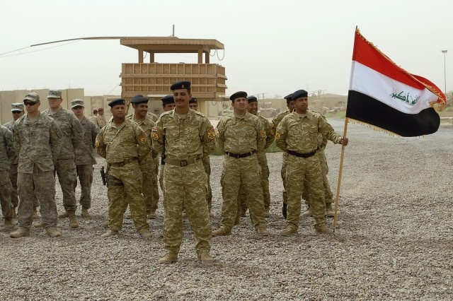 BAGHDAD - Iraqi Soldiers serving with the 1st Battalion, 22nd Brigade, 6th Iraqi Army Division (center) stand in formation among  Soldiers serving with the 1st Combined Arms Battalion, 18th Infantry Regiment, 2nd Heavy Brigade Combat Team, 1st Infantry Division, Multi-National Division-Baghdad at Joint Security Station Hurriyah II, June 9 . The JSS transfers to the Iraqi Army with a ceremony highlighting the security agreement signed between the U.S. Government and the Government of Iraq.