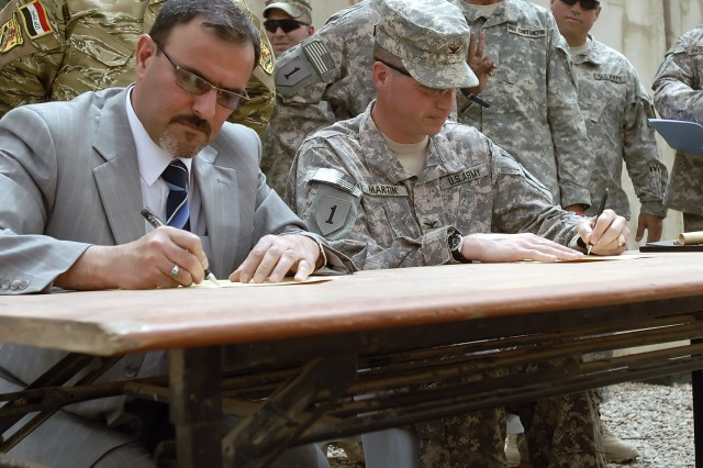 BAGHDAD - Col. Joseph Martin (right), a native of Dearborn, Mich., commander, 2nd Heavy Brigade Combat Team, 1st Infantry Division, Multi-National Division-Baghdad, and Samir Haddad, a representative of the Office of the Prime Minister of Iraq, sign the official documents stating Joint Security Station Hurriyah II is in full control of the Iraqi Army in Kadamiyah, June 9.
