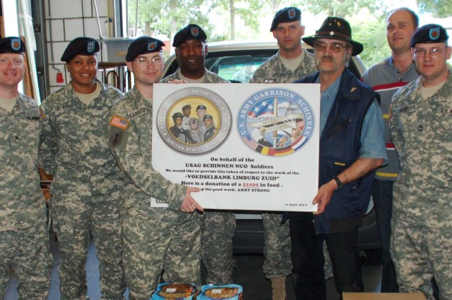 SCHINNEN. Netherlands -- U.S. Army Garrison Schinnen noncommissioned officers mark their June 19, 2009 donation of $1,000 worth of food items with South Limburg Food Bank Coordinator, Harrie Verweij (center right) with the presentation of a poster that will hang inside the premises of the food bank.