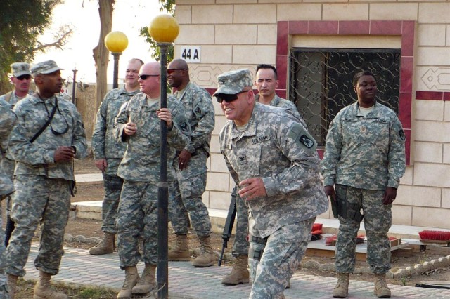 Col. Mark E. Drake, 10th Sustainment Brigade commander and a native of St. Paul, Minn., enjoys a game of corn-hole with Soldiers at Camp Taji, Iraq.