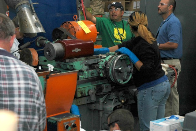 """(Corpus Christi, TX) - One of four Corpus Christi Army Depot teams are shown working through cleaning and inspecting their assigned grinder as part of the Total Production Maintenance program that integrates operators and maintainers. This process aids in keeping the equipment ready for production. """""""