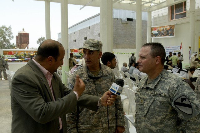 BAGHDAD - Maj. Jeffrey Schrick, a native of Frederick, Okla., commander, 2nd Battalion, 8th Cavalry Regiment, operationally attached to the 2nd Heavy Brigade Combat Team, 1st Infantry Division, Multi-National Division - Baghdad, speaks with a member of the Arabic media at the grand opening of the Nasir Wa Salam Fire Station in the  Abu Ghraib district west of Baghdad June 11. The fire station will provide a service to the community that was not offered previously.