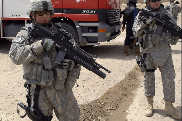 BAGHDAD - Sgt. Jason Powell, a native of Fort Lauderdale, Fla., assigned to a personal security detachment with the 2nd Heavy Brigade Combat Team, 1st Infantry Division, Multi-National Division - Baghdad, helps secure the surrounding area of the Nasir Wa Salam Fire Station in Abu Ghraib June 11. Elements of the brigade and local leaders of Abu Ghraib hosted the grand opening for the fire station, which celebrated the continued partnership between the U.S. and Iraq.