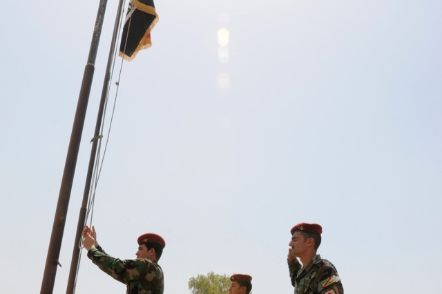 CONTINGENCY OPERATING BASE SPEICHER, TIKRIT, Iraq -An Iraqi Soldier hoists the Iraqi flag during a transfer of authority ceremony to signify the opening of the Balad Joint Coordination Center, which previously was 3rd Squadron, 4th Calvary Regiment, 3rd Infantry Brigade Combat Team, 25th Infantry Division's Forward Operating Base Paliwoda, June 15.