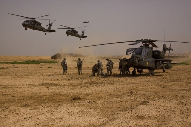 TAJI, Iraq - During a downed aircraft training exersice, Soldiers of Company F, 3rd Battalion, 1st Air Cavalry Brigade, 1st Cavarly Division, Multi-National Division - Baghdad, go through the motions of treating the pilots as two UH-60 Black Hawk Helicopters from 3rd Bn., 1st ACB, bring in the downed aircraft recovery team to a training site, at Camp Taji, Iraq, north of Baghdad, June 10.