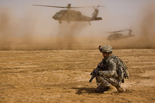 TAJI, Iraq - Sgt. Ryan Crook, from Orange Park, Fla., a team leader in Company F, 3rd Battalion, 1st Air Cavalry Brigade, 1st Cavalry Division, Multi-National Division - Baghdad, pulls security as two UH-60 Black Hawk helicopters depart the training site at Camp Taji, Iraq, north of Baghdad, June 10, during a downed aircraft training exercise.  The training was conducted to fine tune the planning and execution of the mission in case of the actual event.