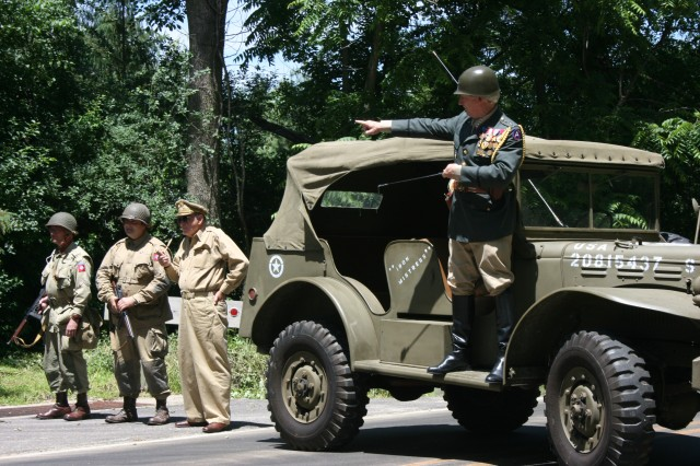 Reenactors assist with directing traffic as the cross country convoy arrives at Cantigny 20 June 2009 to rest, refuel and share their experiences with the local community near Chicago.  The Convoy is retracing the route of the first major motorized expedition across the United States.