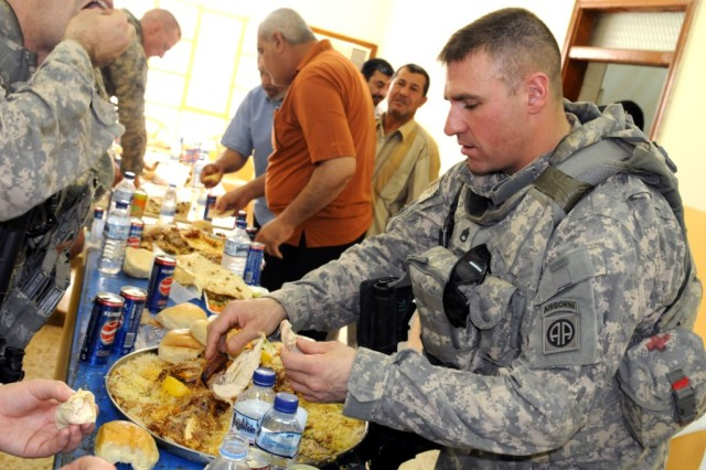 BAGHDAD - Staff Sgt. Richard Smith, of Tulsa, Okla., enjoys some Iraqi cuisine during the opening ceremony of a new civil support district center building June 11 in the city of Shawa Wa Um Jidir, located in the 9 Nissan District of eastern Baghdad. The center will offer hundreds of Iraqi civilians courses in road repair, generator repair, plumbing, electrical installation, sanitation and landscaping in order for them to find work in their local neighborhoods in their chosen career paths.