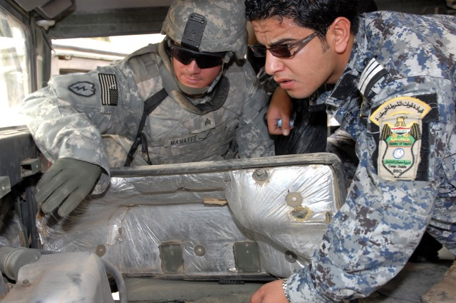 """BAGHDAD - """"Everything I showed them, I wanted them to also do instead of just talking to them about it,"""" said North Wilkesboro, N.C., native, Sgt. Adam Mahaffey (left), an infantryman assigned to Company A, 252nd Combined Arms Battalion, 30th Heavy Brigade Combat Team, as he points out a vent to Sgt. Saefe Fadhel Nassir (right), a driver assigned to 1st Co., 3rd Bn., 7th Bde., 2nd National Police Division, during a humvee maintenance class in Doura, here, June 12. """"You can't learn if you've never been in a vehicle,"""" Mahaffey added."""